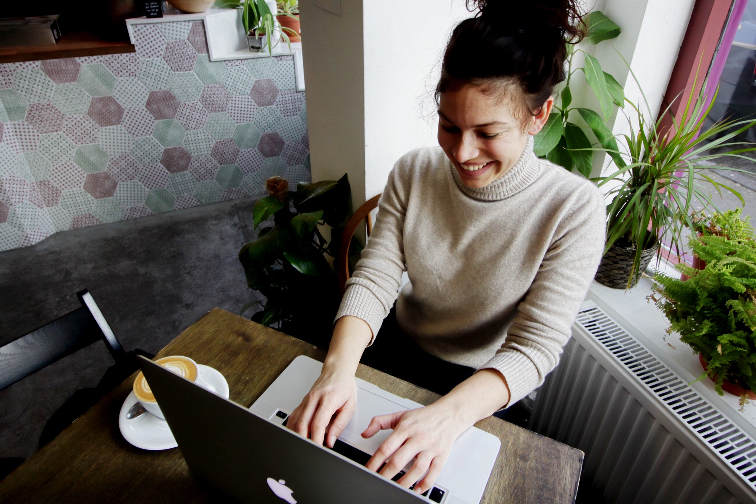 "A woman smiles as she types on her laptop from the Heed PR post ""5 Essential Traits In Good PR Professionals"""