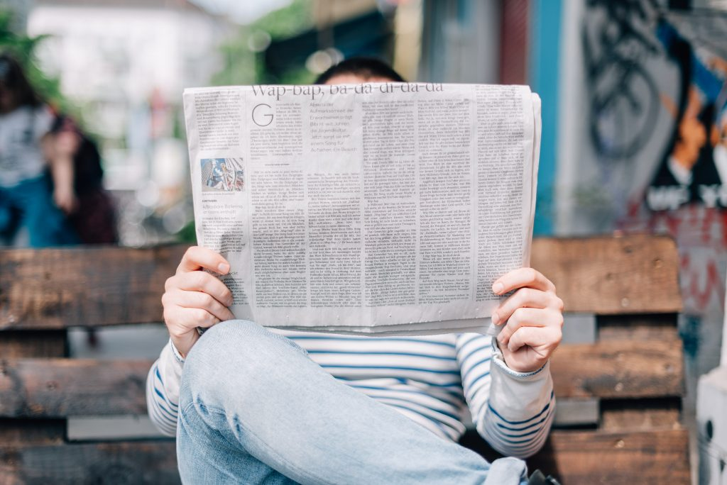 """A man reads a newspaper from the Heed PR post """"What Do Reporters Hate? Don't Commit These 5 PR Sins"""""""